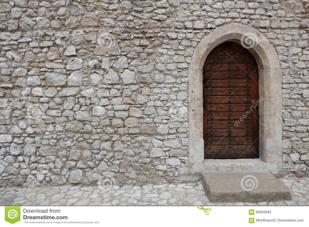 Fortress or castle wall made of stacked stone blocks and a wooden door with gothic style pointed arch