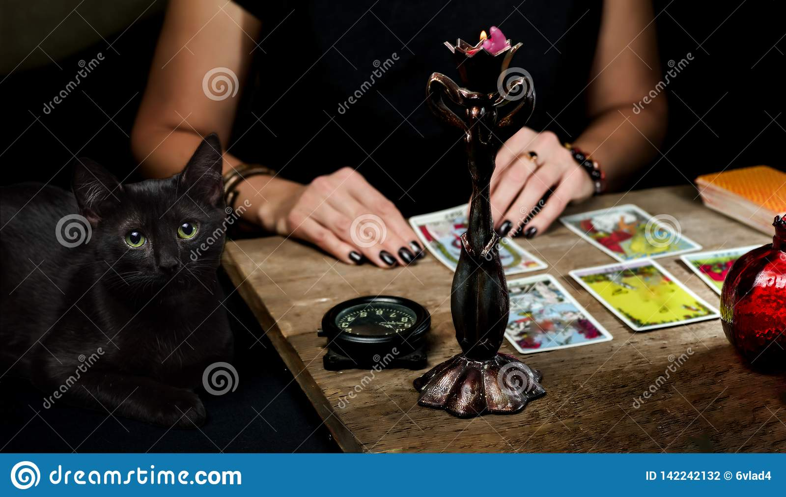 The fortune teller lays out on a wooden table the tarot cards by the light of a candle. Black cat sitting near the table.