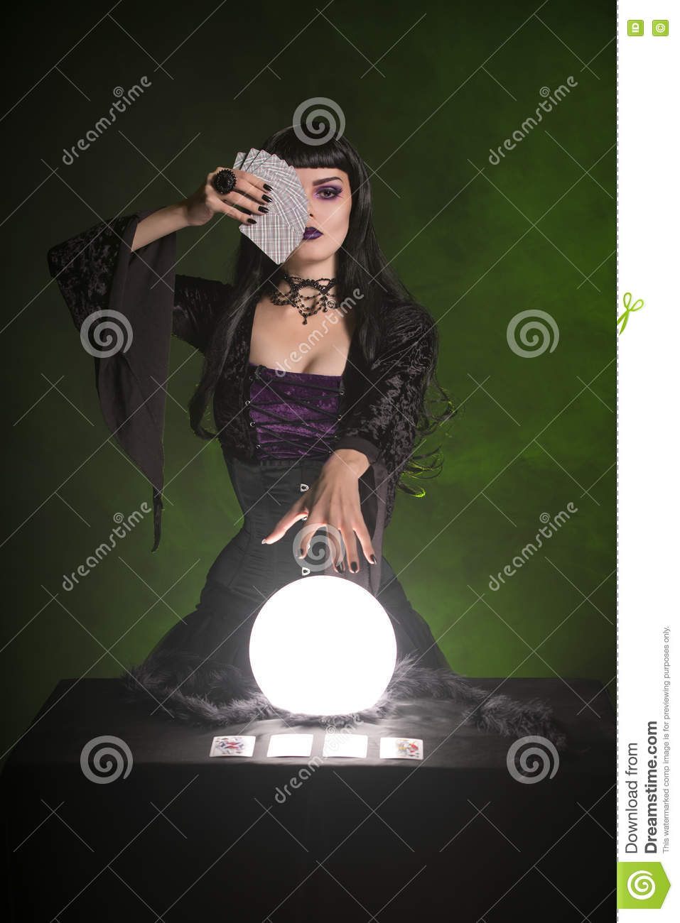 Fortune teller with playing cards and crystal ball