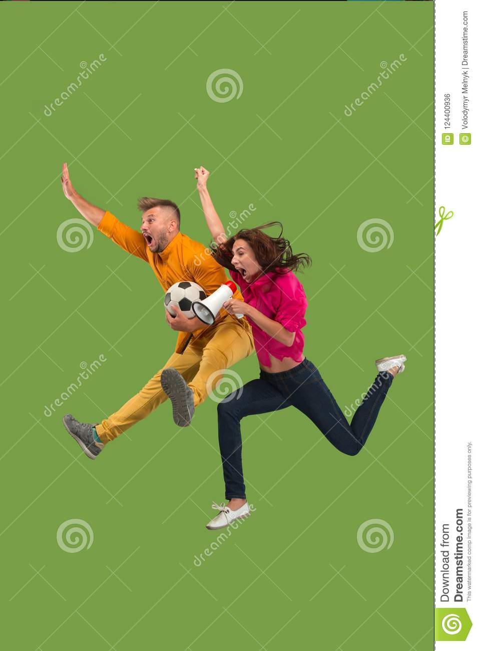 Forward to the victory.The young couple as soccer football player jumping and kicking the ball at studio on a green