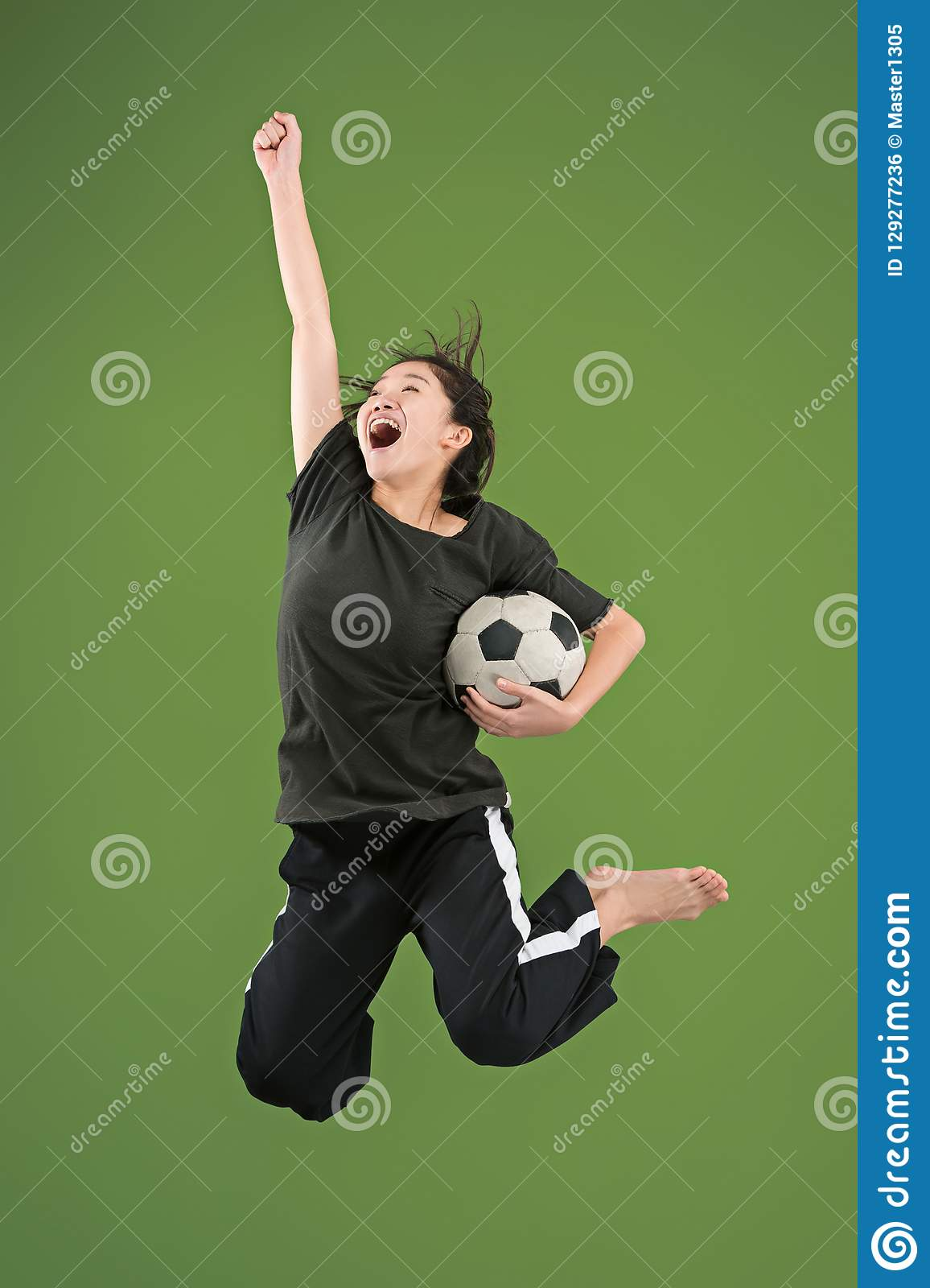 Forward to the victory.The young woman as soccer football player jumping and kicking the ball at studio on green