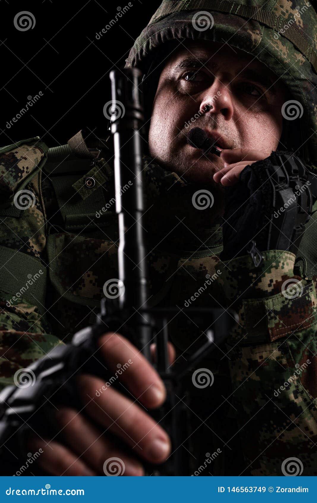 Forze speciali del soldato con il fucile su fondo scuro