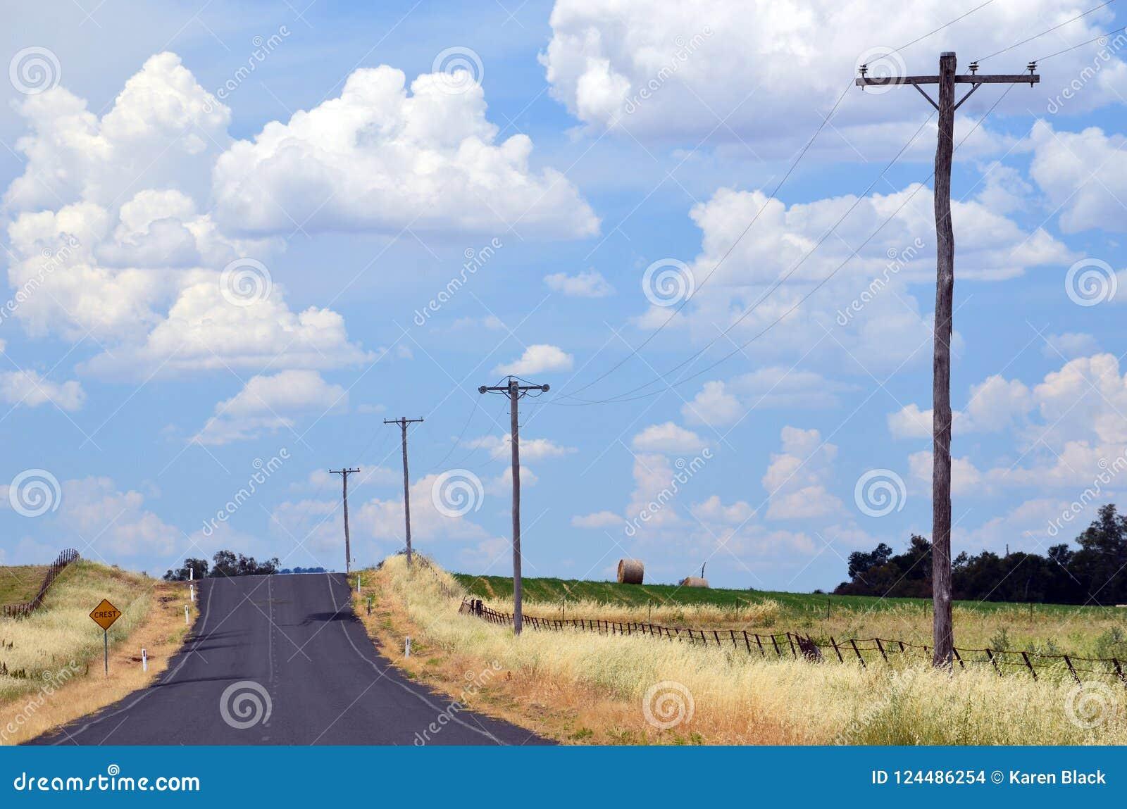 Foschia di calore di estate su una strada campestre attraverso terreno coltivabile