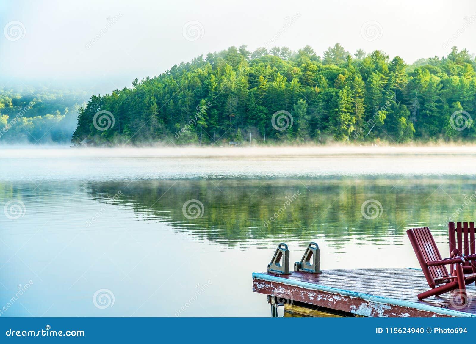 Foschia di primo mattino con il bacino e le sedie di legno rosse