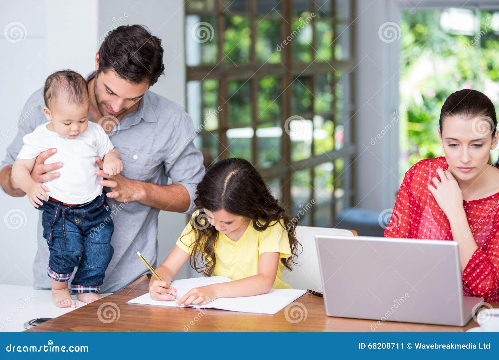 Fostra genom att använda bärbar datordottern som gör läxa med fadern