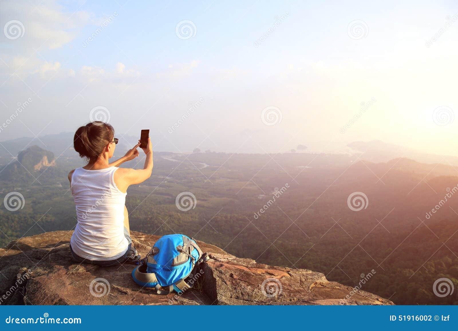 Fotógrafo da mulher que toma fotos no pico de montanha