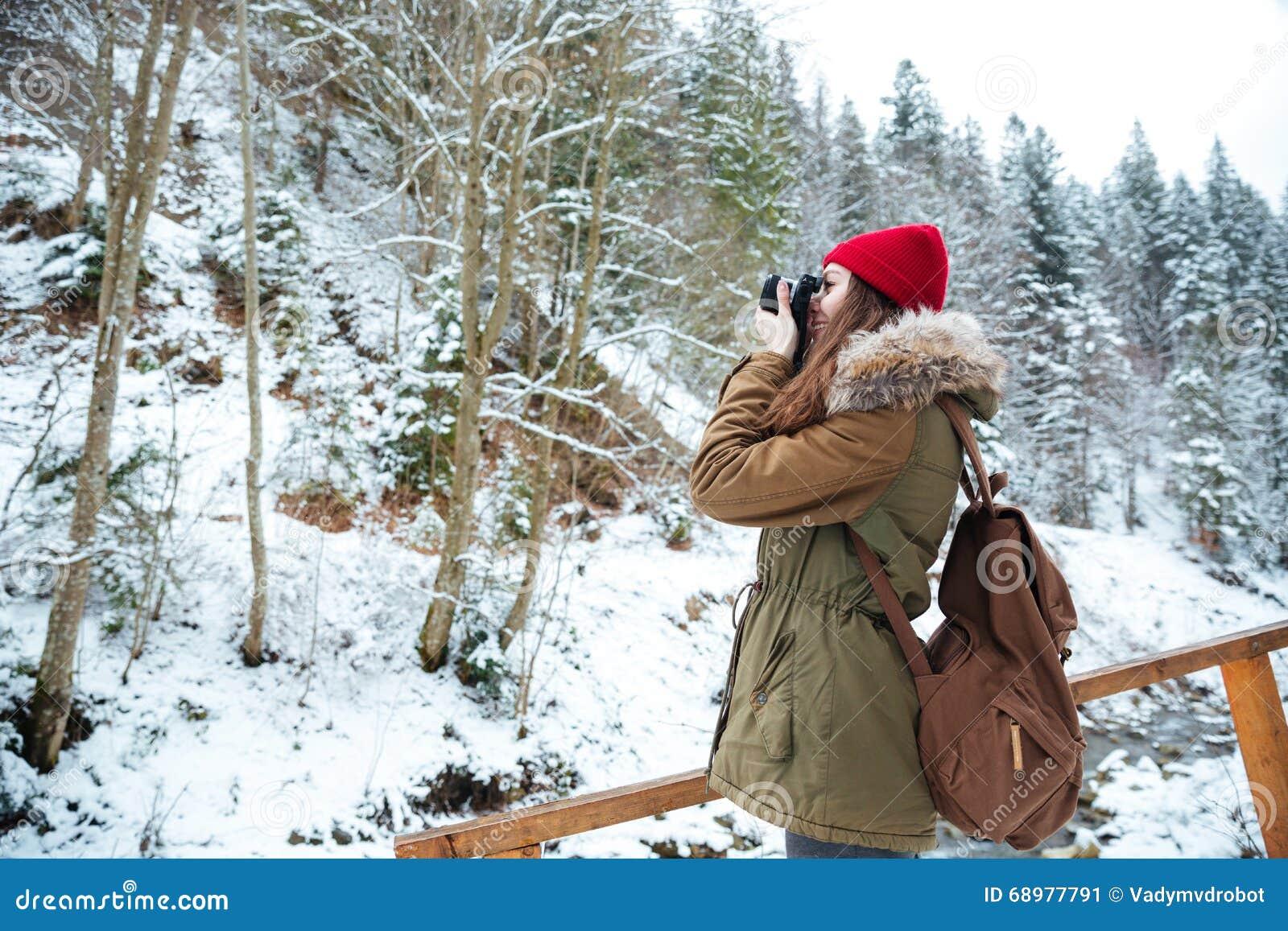 Fotógrafo de la mujer de Concenrated que coloca y que toma imágenes en montañas
