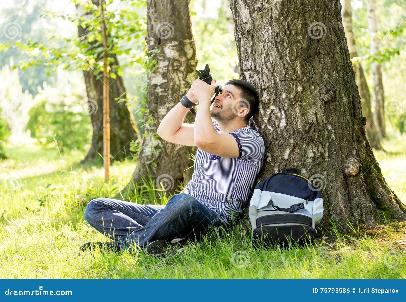 Fotógrafo de sexo masculino joven que fotografía la naturaleza el día de  verano