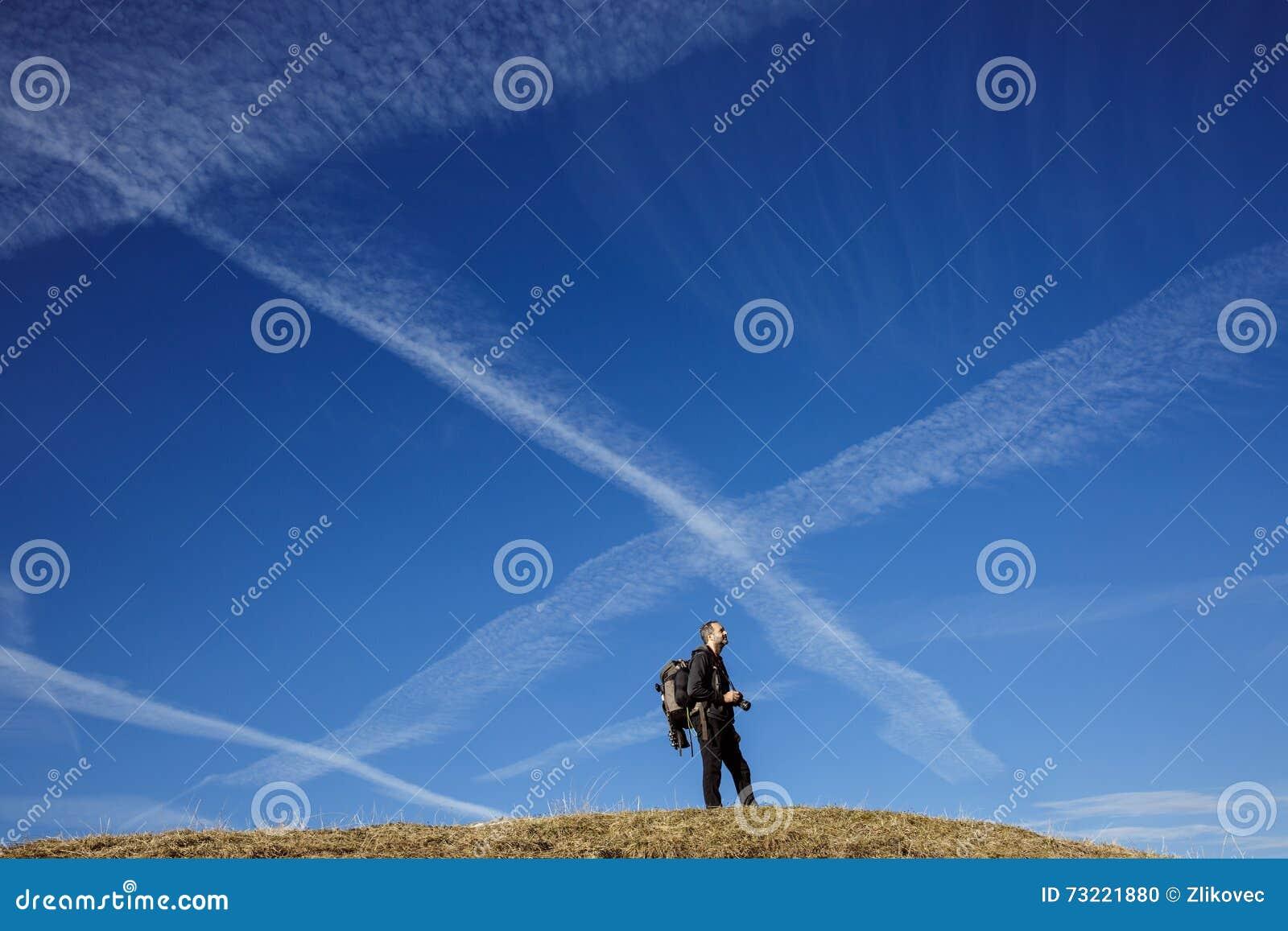 Fotógrafo del caminante en un top de la montaña