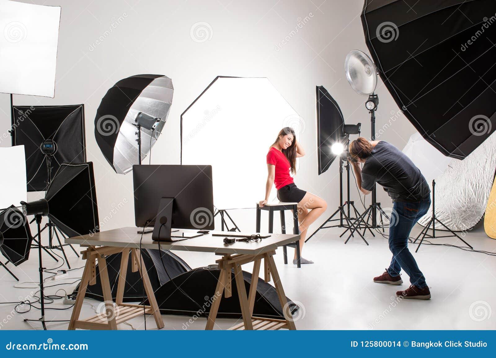 Fotógrafo e modelo bonito que trabalham no estúdio moderno da iluminação
