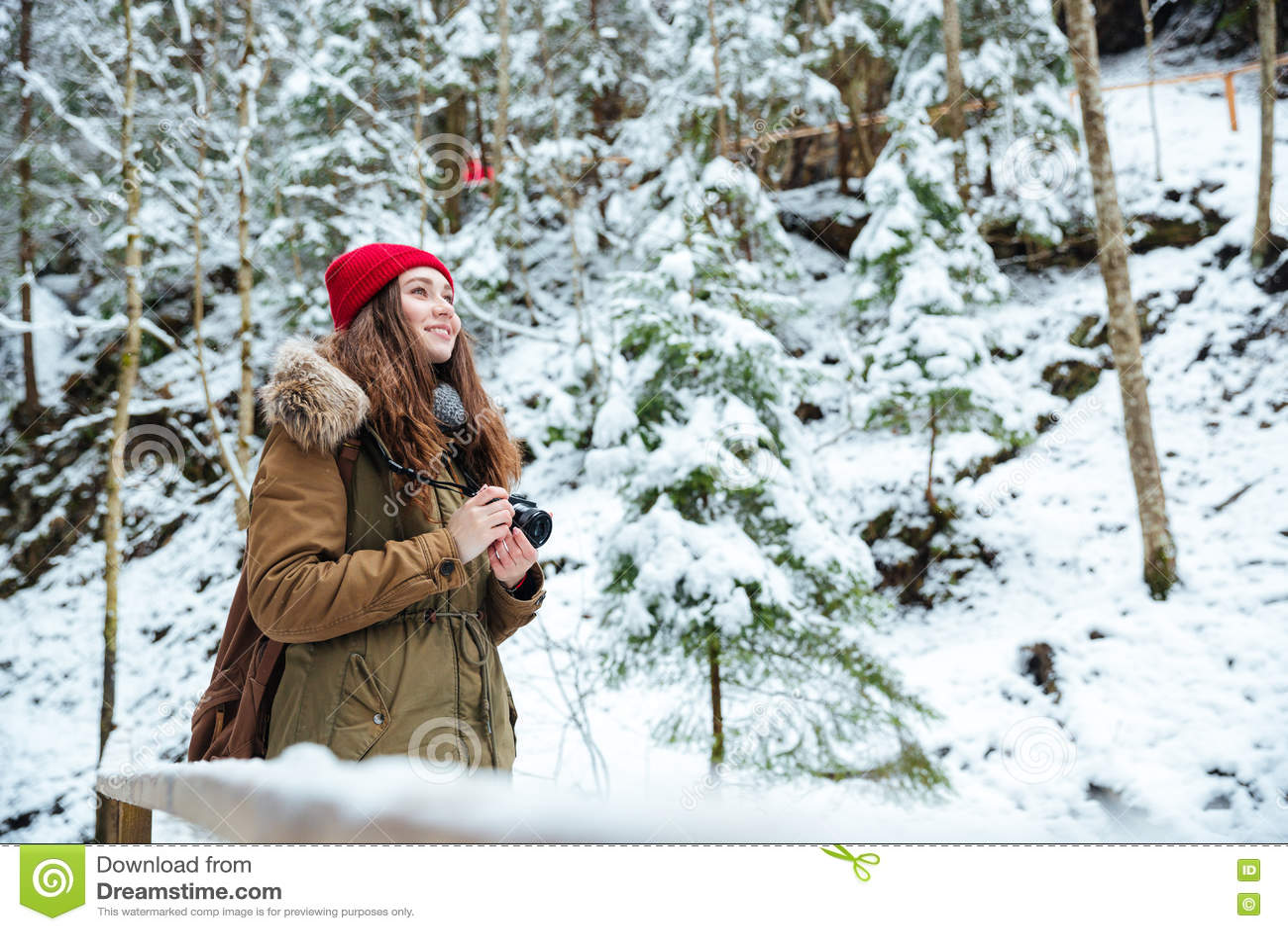 Fotógrafo inspirado sonriente de la mujer que toma las fotos en el bosque en invierno