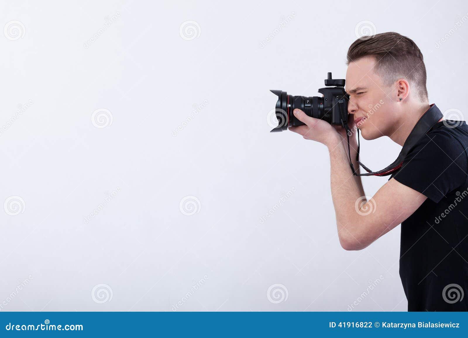 Fotógrafo joven en el fondo blanco