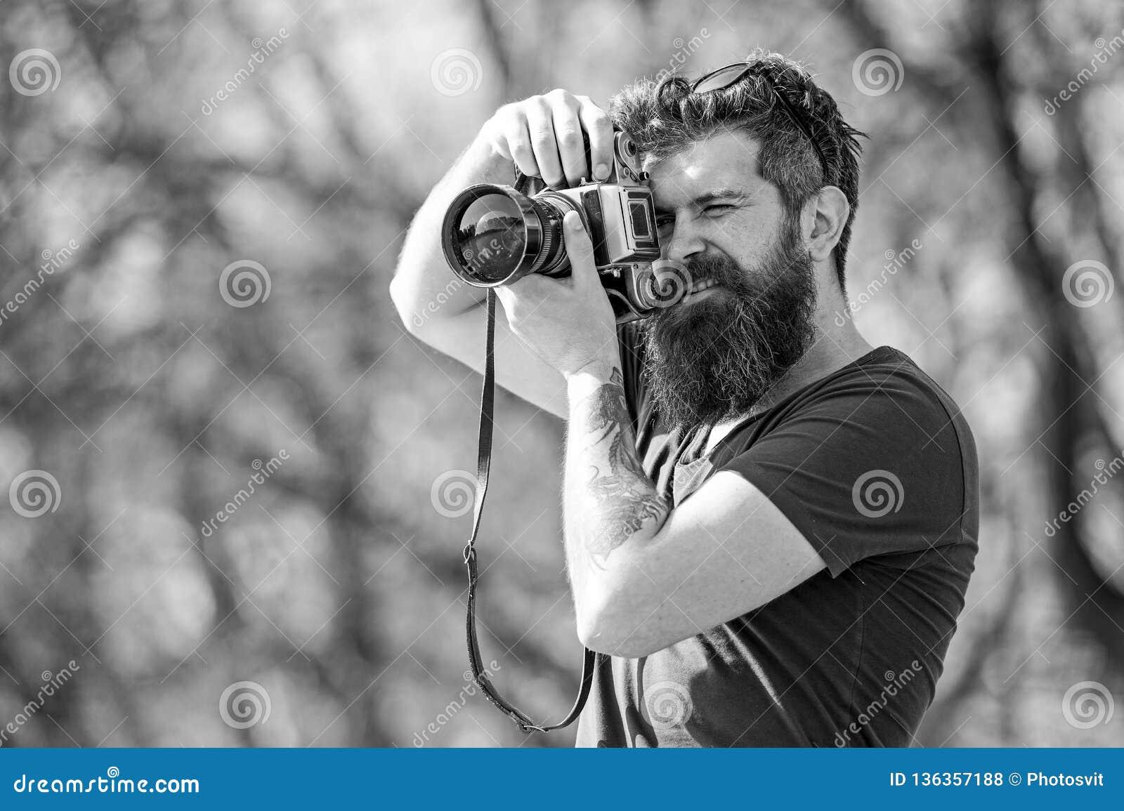 Fotógrafo masculino novo que toma imagens no parque com câmera do vintage, passatempo e conceito da atividade de lazer bearded
