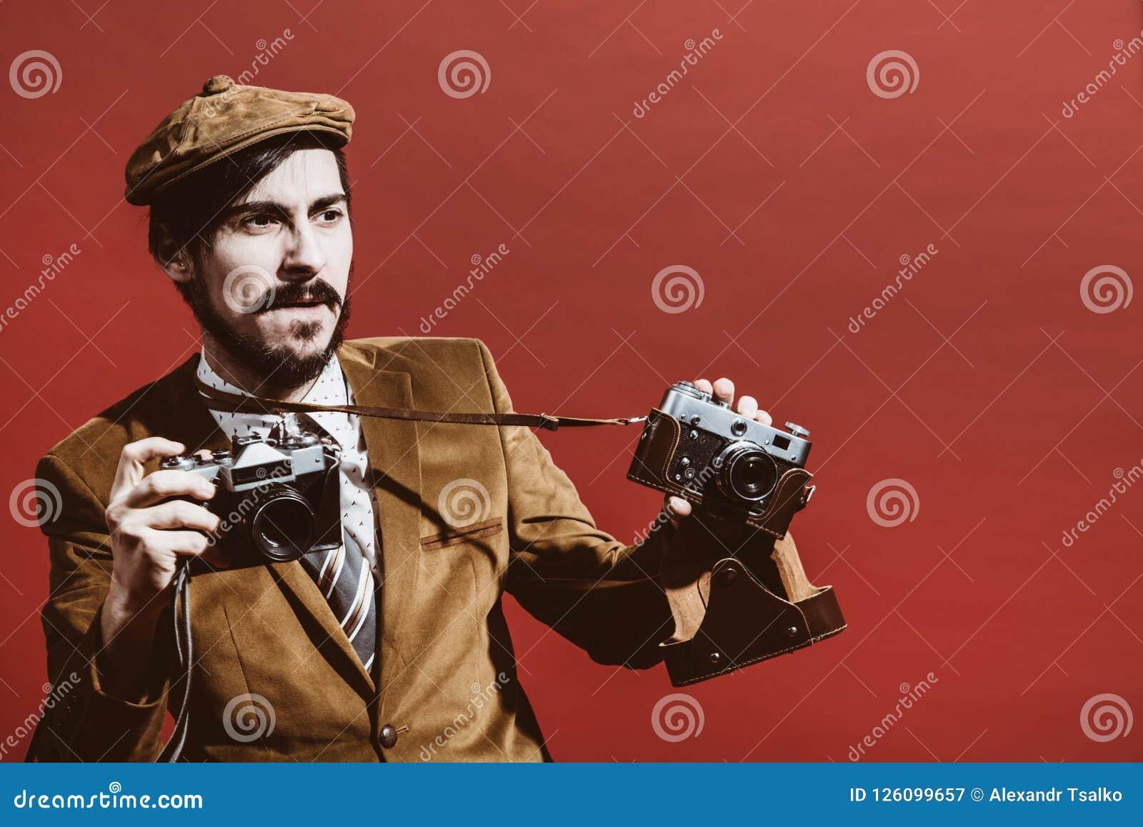 Fotógrafo muy positivo que presenta en estudio con las cámaras
