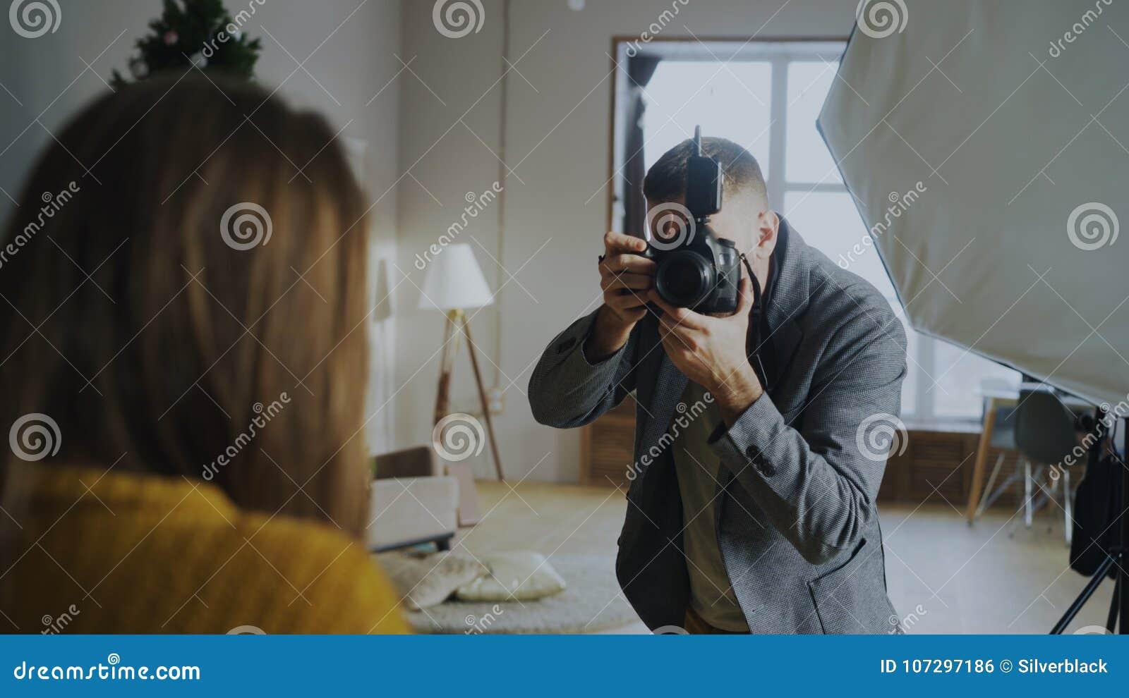 Fotógrafo profesional que toma las fotos del modelo en la cámara digital que trabaja en estudio de la foto