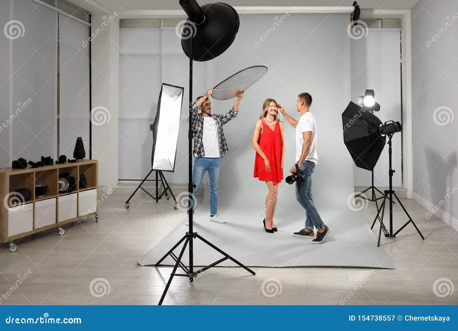 Fotógrafo profissional e assistente que trabalham com modelo em moderno