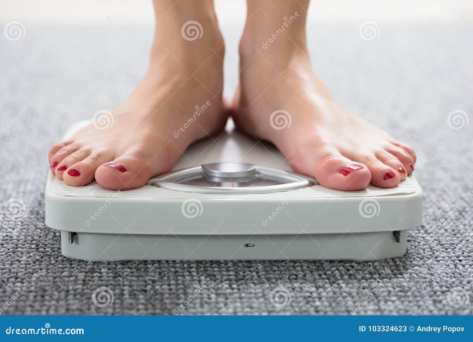 Fot för kvinna` s på skala
