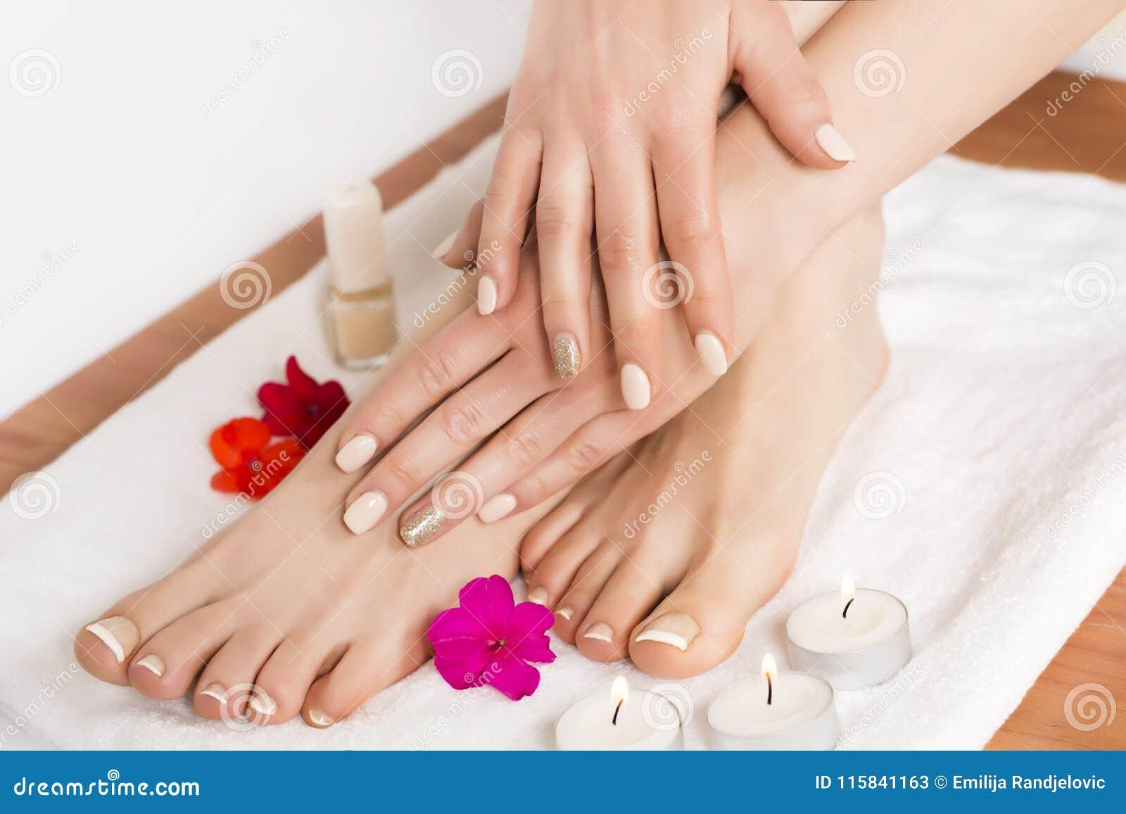 Fot och händer för skönhet kvinnlig på brunnsortsalongen på pedikyrtillvägagångssätt och blommor och stearinljus på den vita hand
