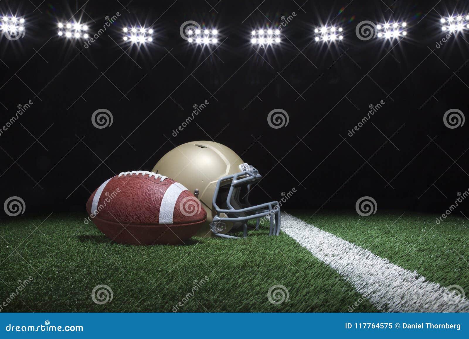 Fotboll och hjälm på gräsfält nedanför stadionljus på natten