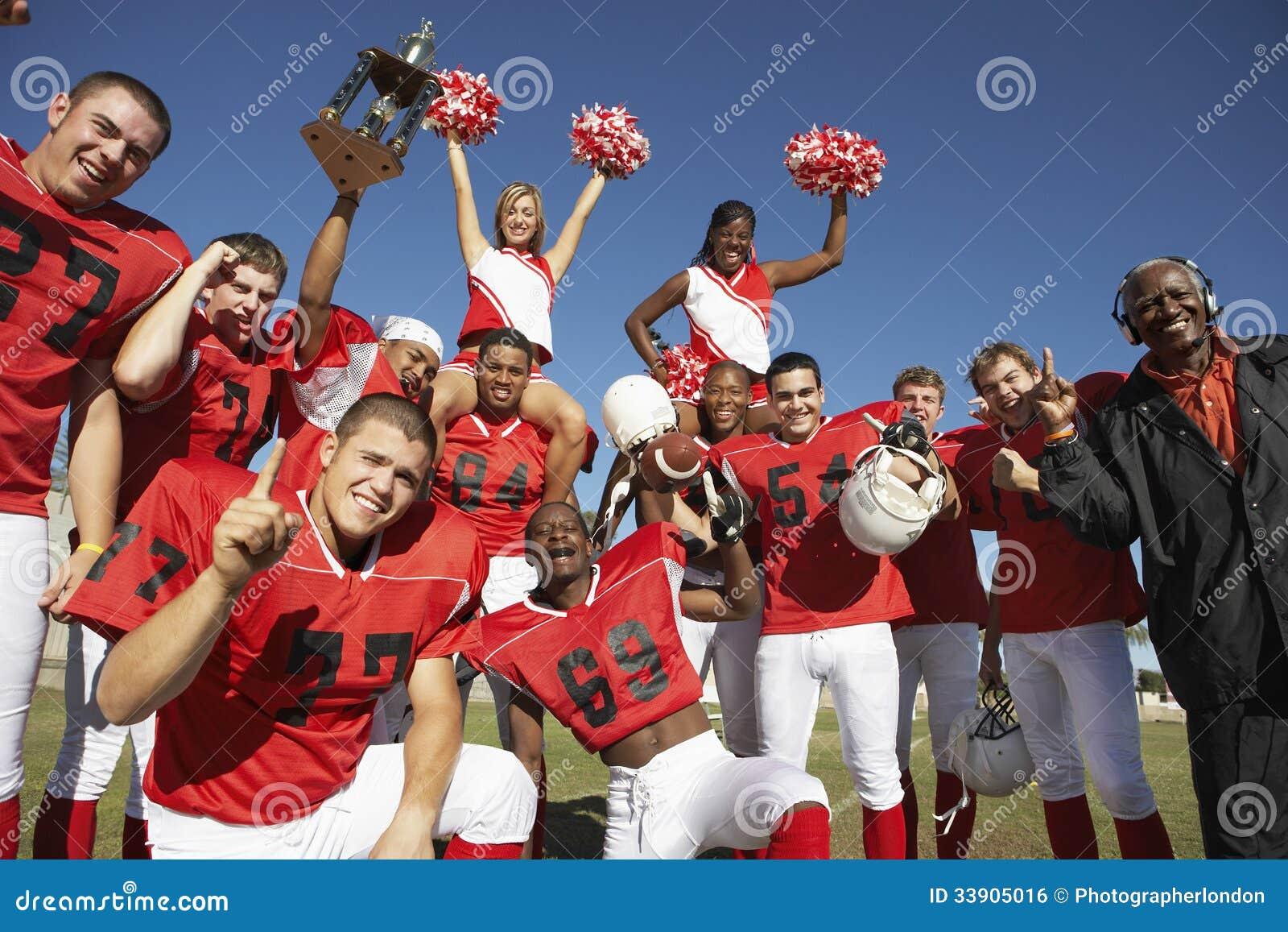 Fotboll Team With Cheerleaders And Coach som firar framgång på fält