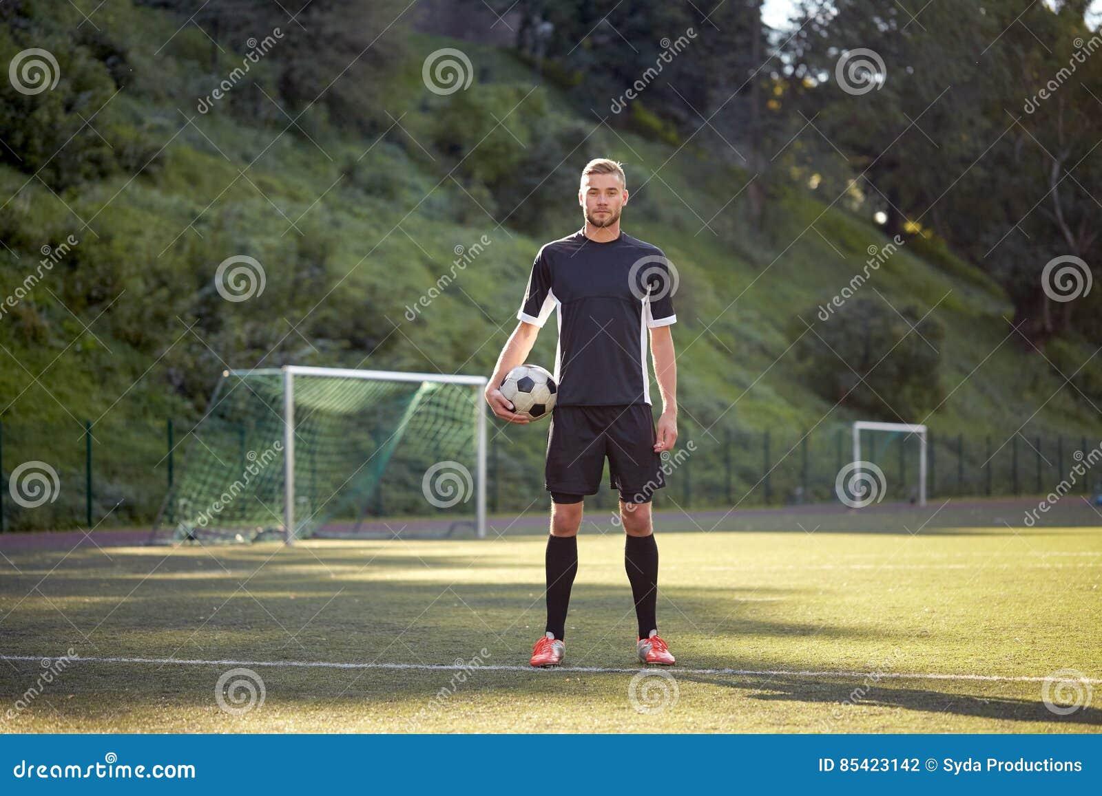 Fotbollspelare med bollen på fotbollfält