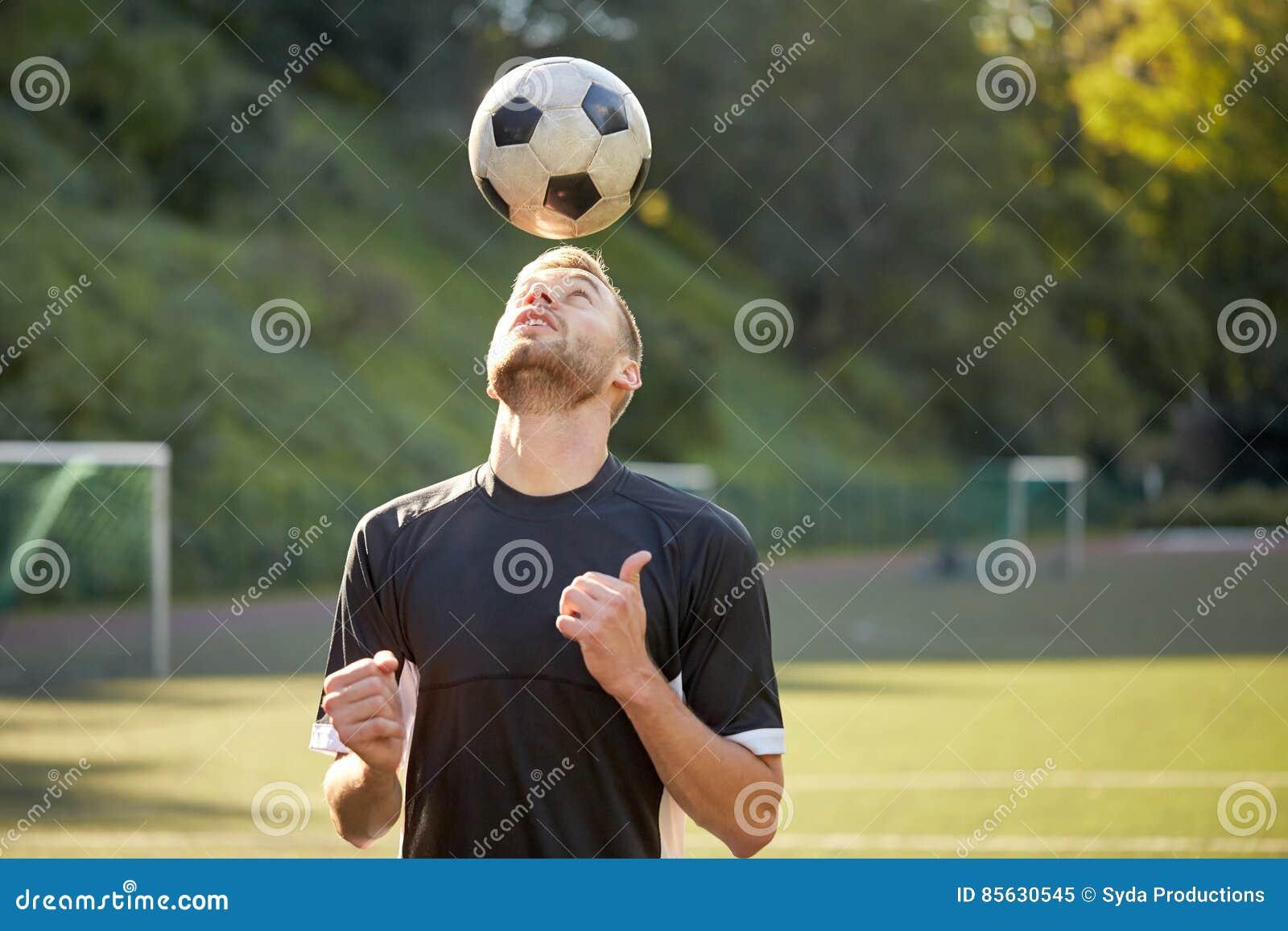 Fotbollspelare som spelar med bollen på fält