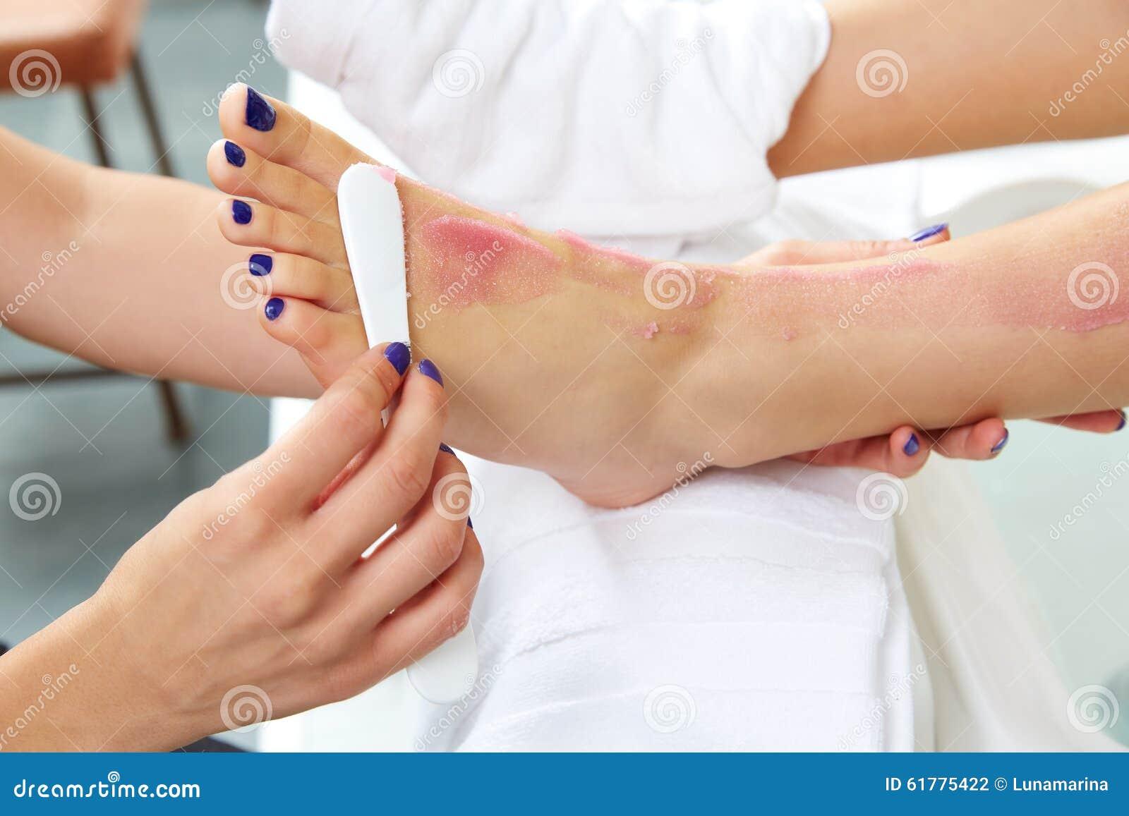 Foten skurar pedikyrkvinnan som benet spikar in salongen