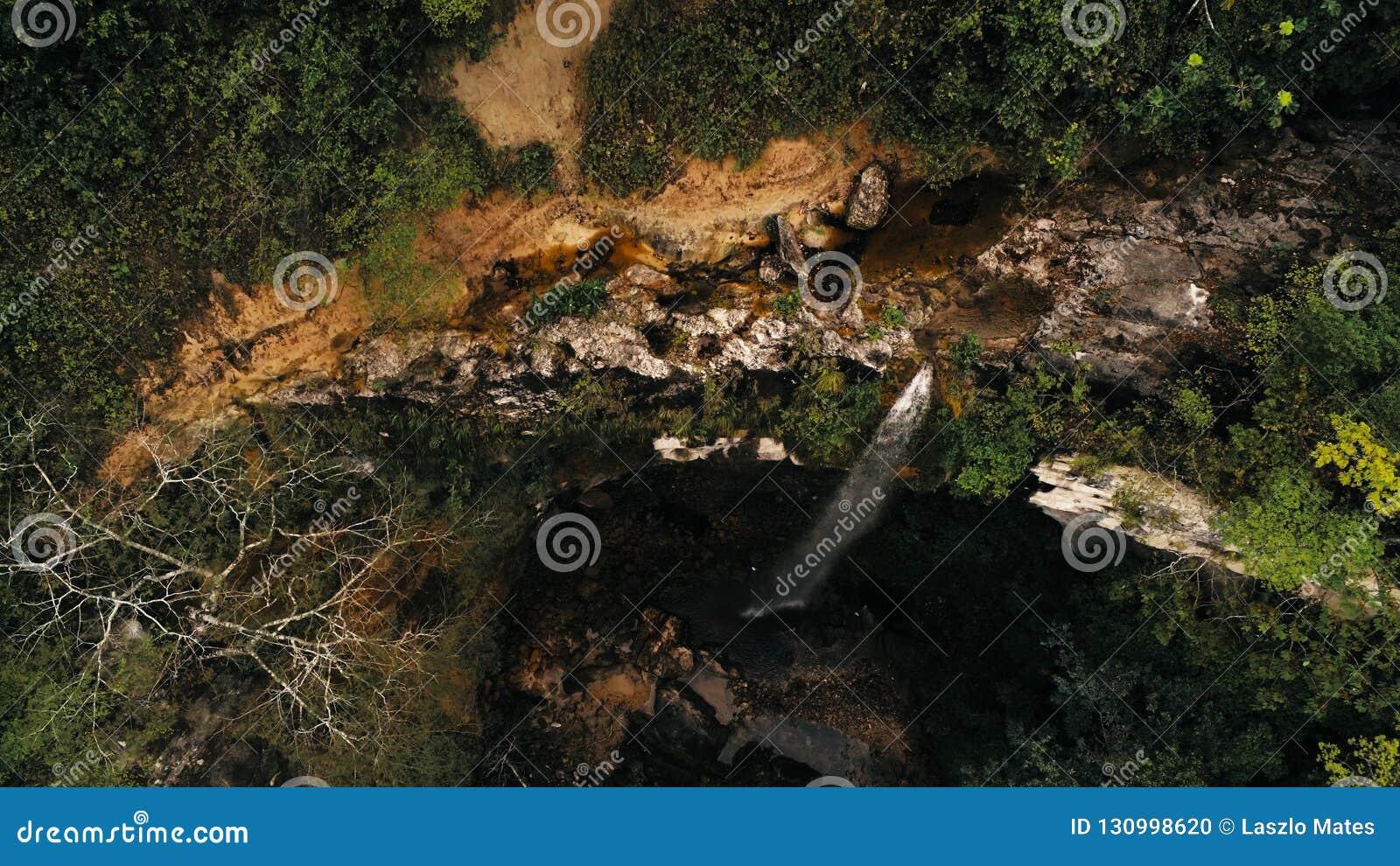 Foto aérea cinemático do zangão da cachoeira e uma associação pequena profundamente na selva da floresta úmida no parque nacional