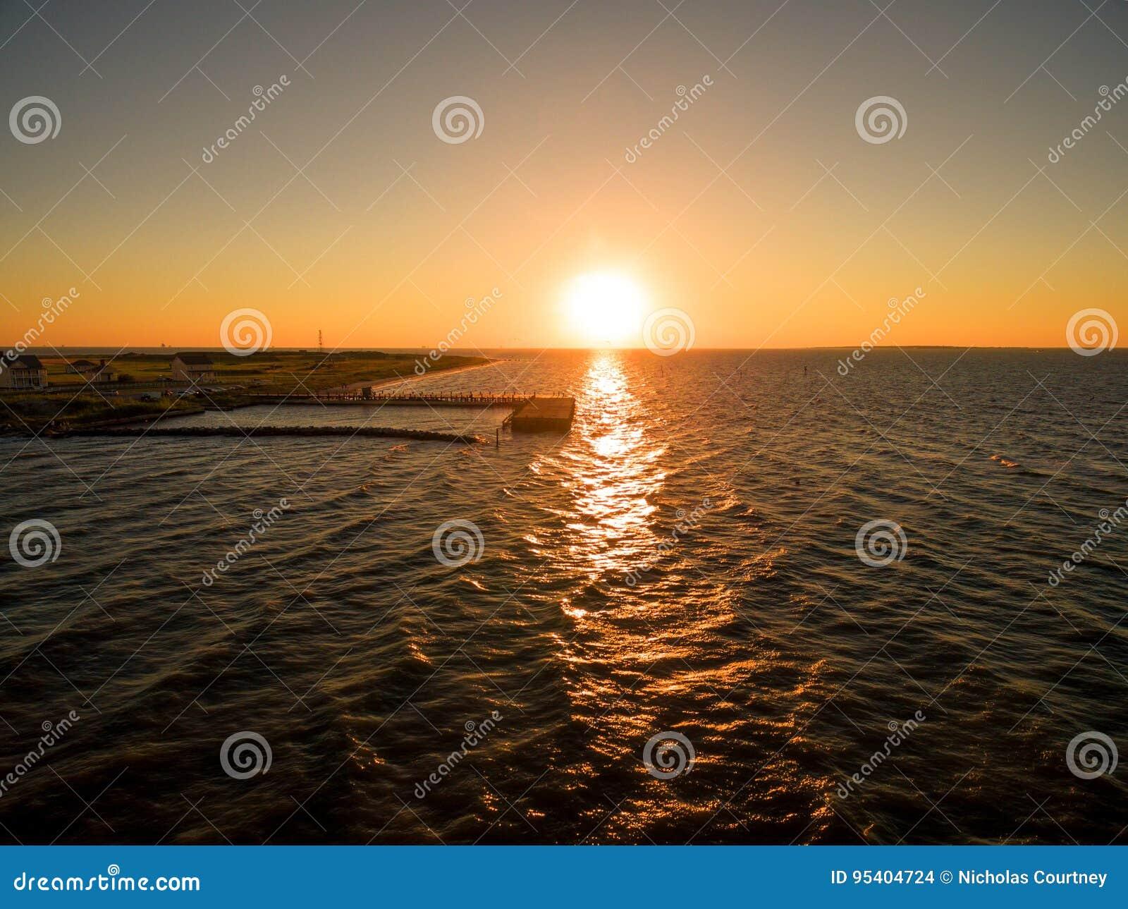 Foto aérea do por do sol do zangão - o por do sol bonito do oceano sobre o forte Morgan/golfo suporta, Alabama