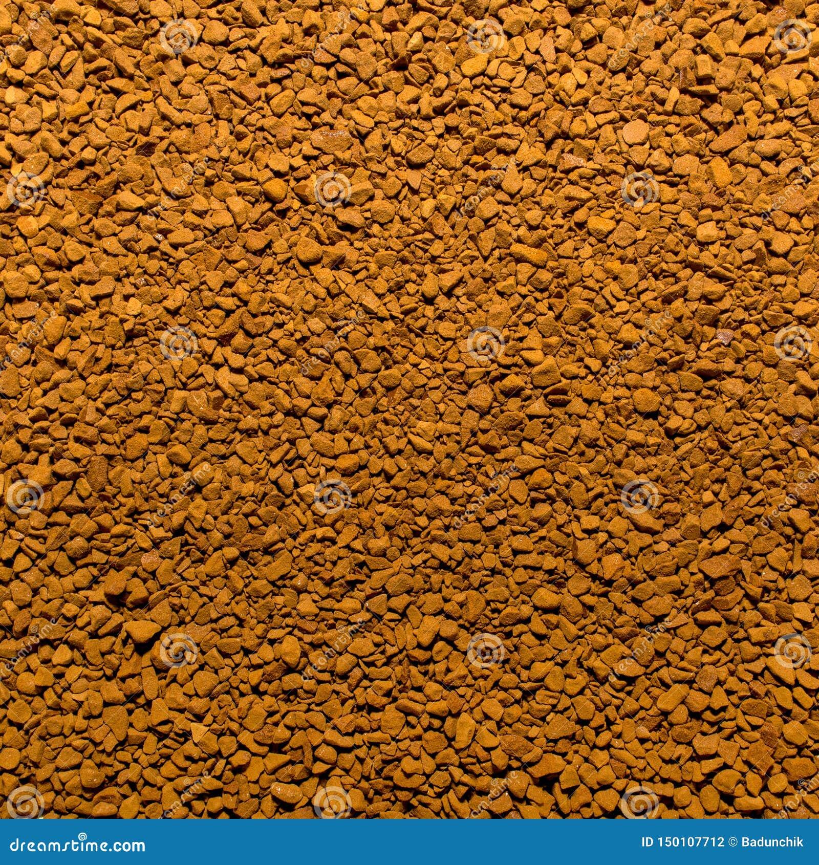 Foto av closeuptextur av brunt malt ögonblickligt kaffe, bakgrund