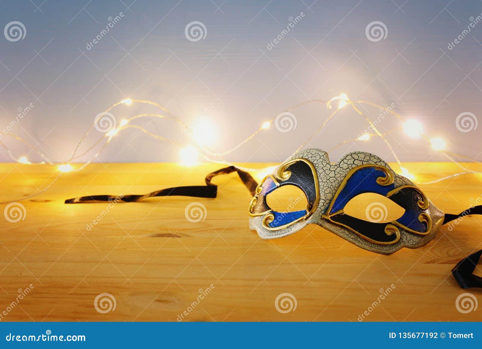 Foto av den eleganta venetian, mardigrasmaskeringen över trätabellen och guld- ljus för girland