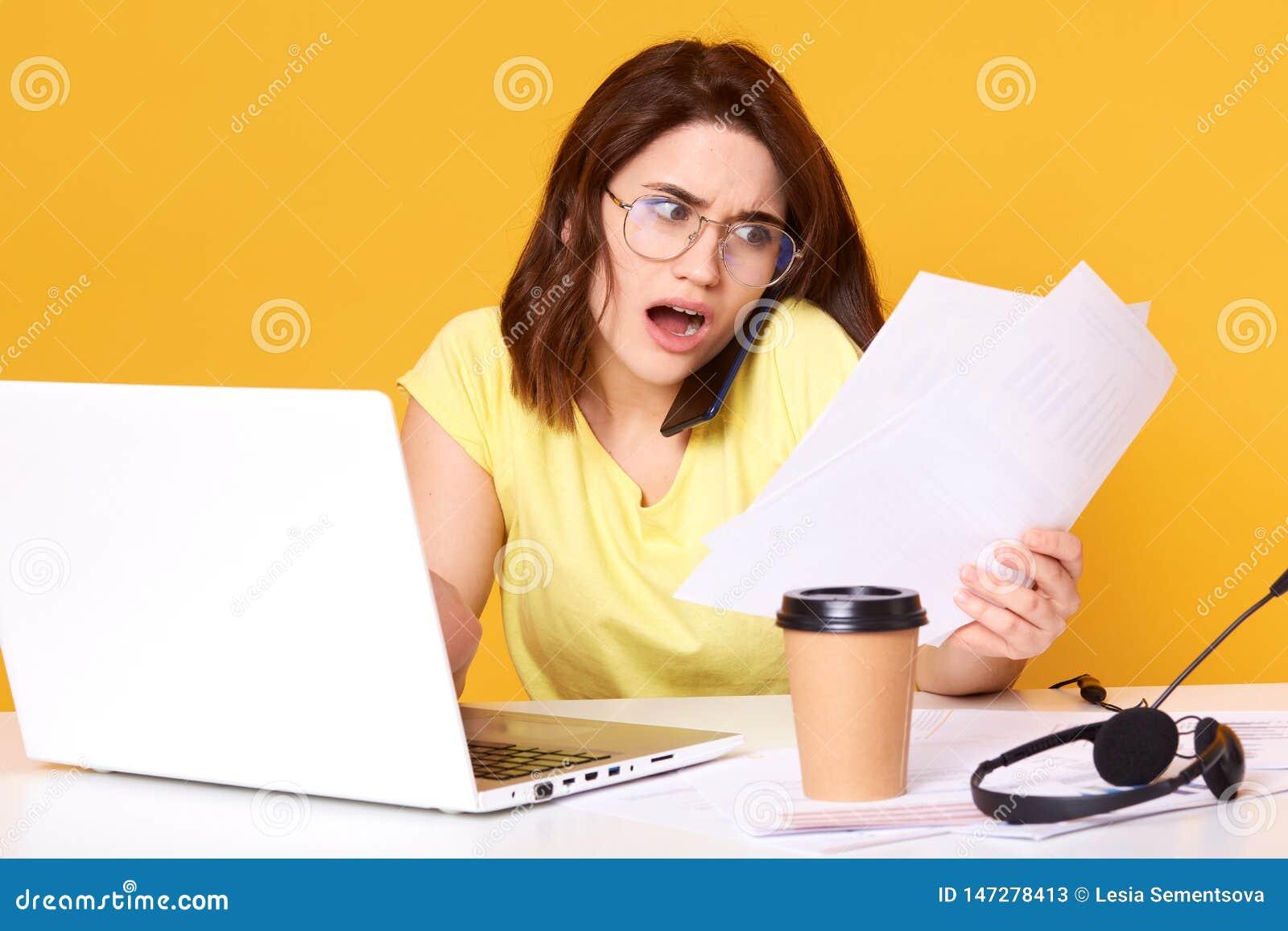 Foto av den spända unga brunettaffärskvinnan som i regeringsställning arbetar med pappers- dokument över gul bakgrund som kontrol