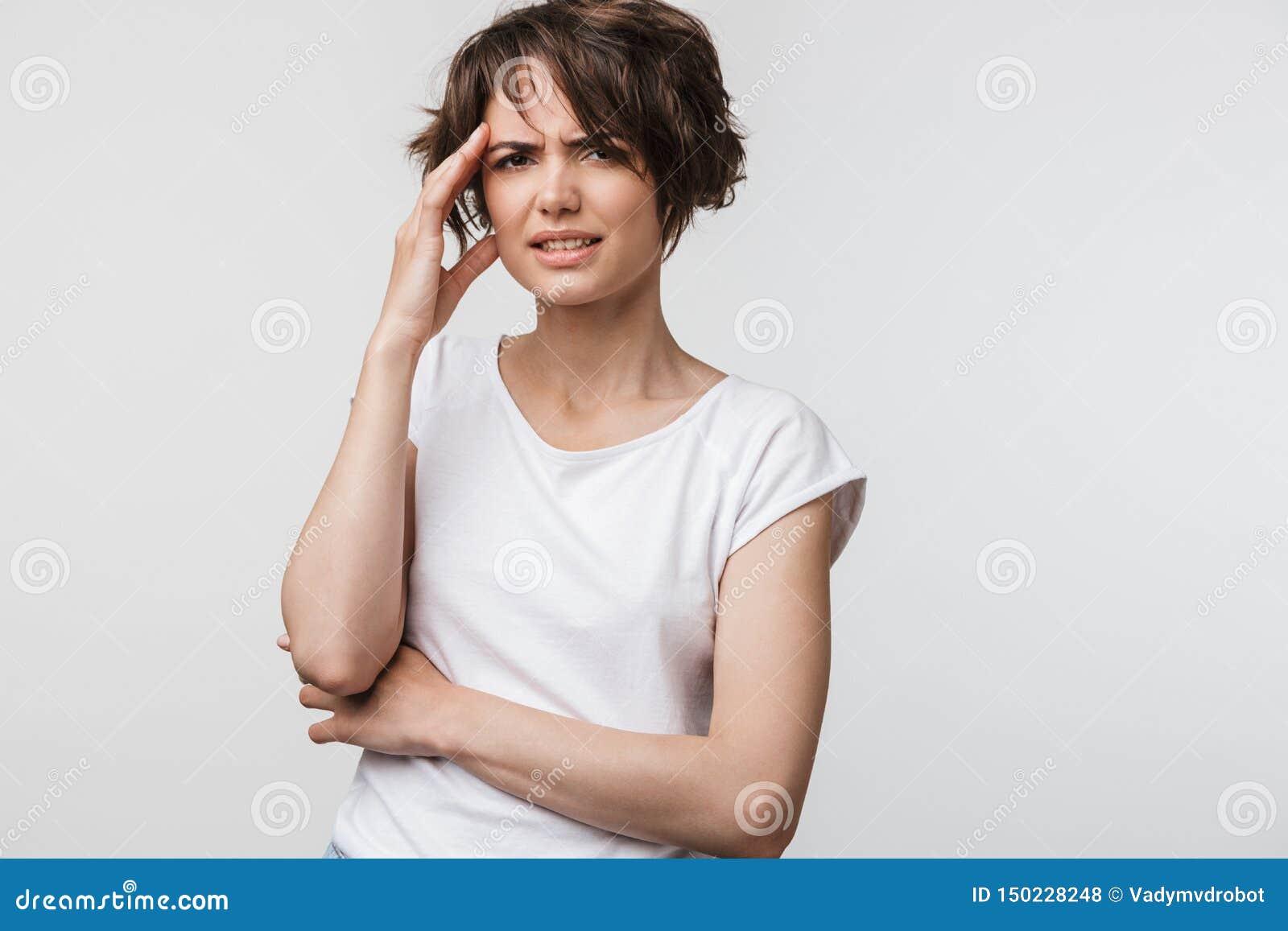 Foto av den upprivna kvinnan med kort brunt hår i den grundläggande t-skjortan som griper hennes huvud och gnider tempel på grund
