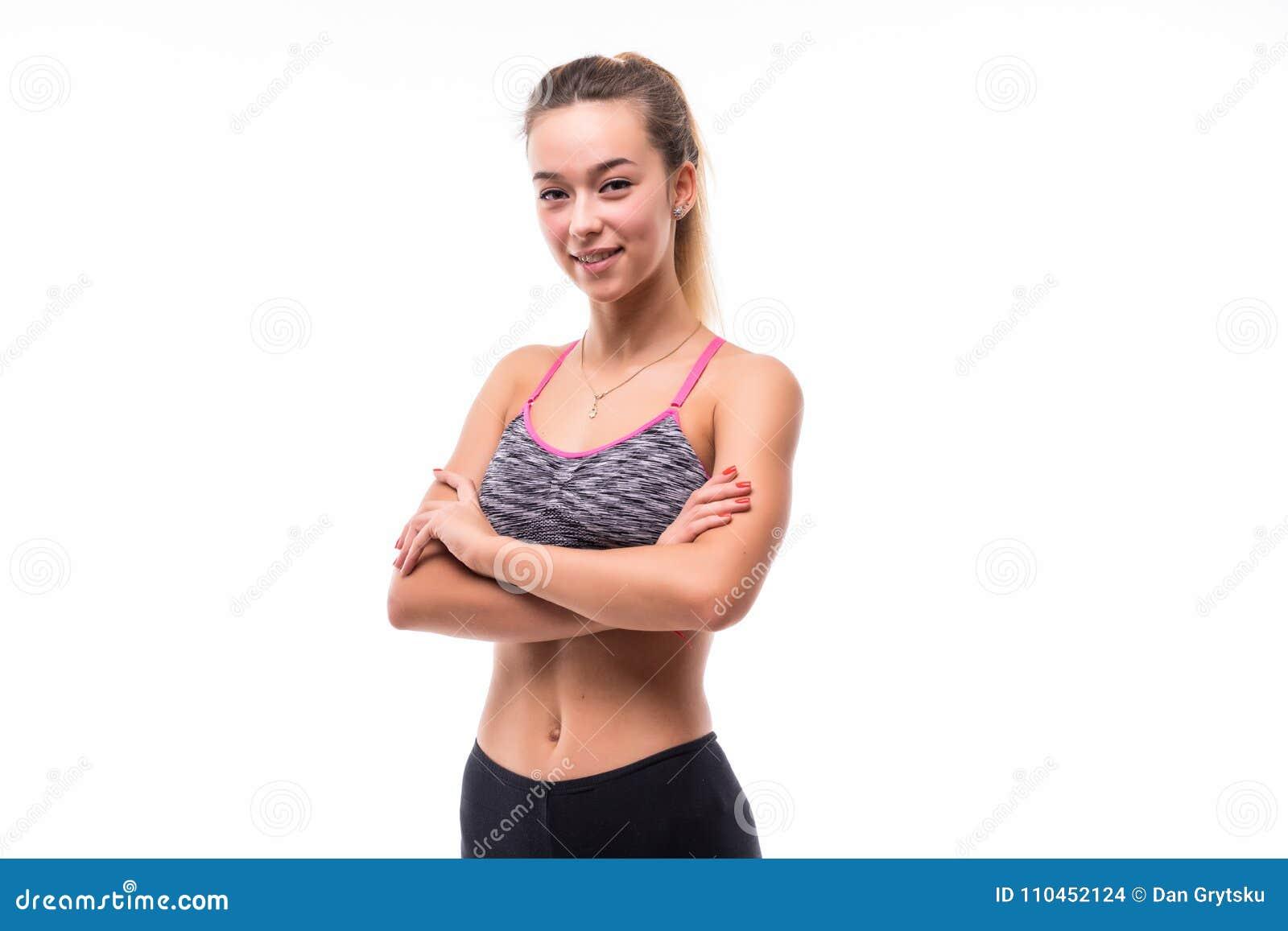 Foto av det gladlynta unga sportkvinnaanseendet som isoleras över vit bakgrund som ser kameran med korsade armar
