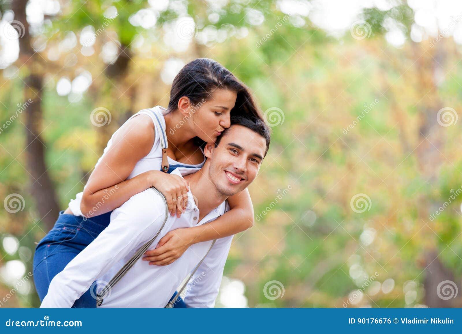 Foto av gulliga par som kramar och kysser på den underbara hösten