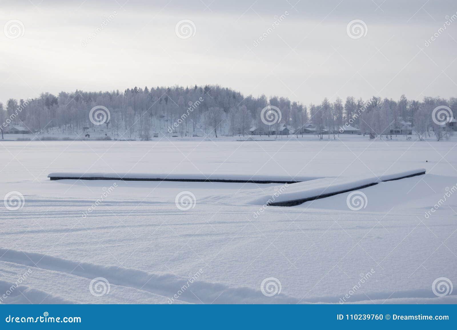 Foto bonita do específico do inverno Lago congelado no inverno Foto com a floresta bonita no fundo e uma doca que encontra-se no