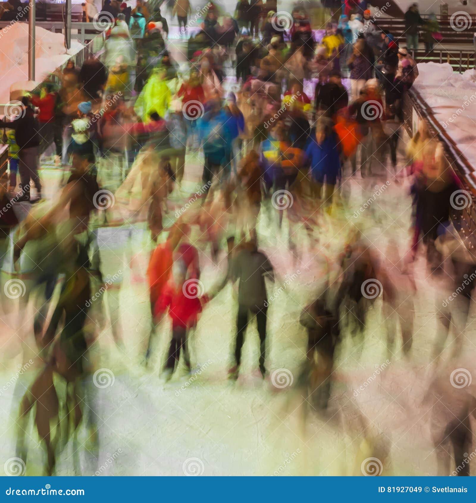 Foto borrada de muitas pessoas que patinam na pista de gelo no tempo da noite fora, parque no inverno Natal, esporte