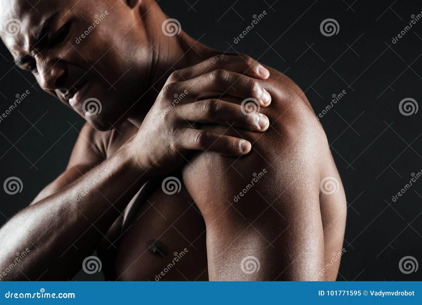 Foto colhida do homem afro-americano descamisado novo com ombro