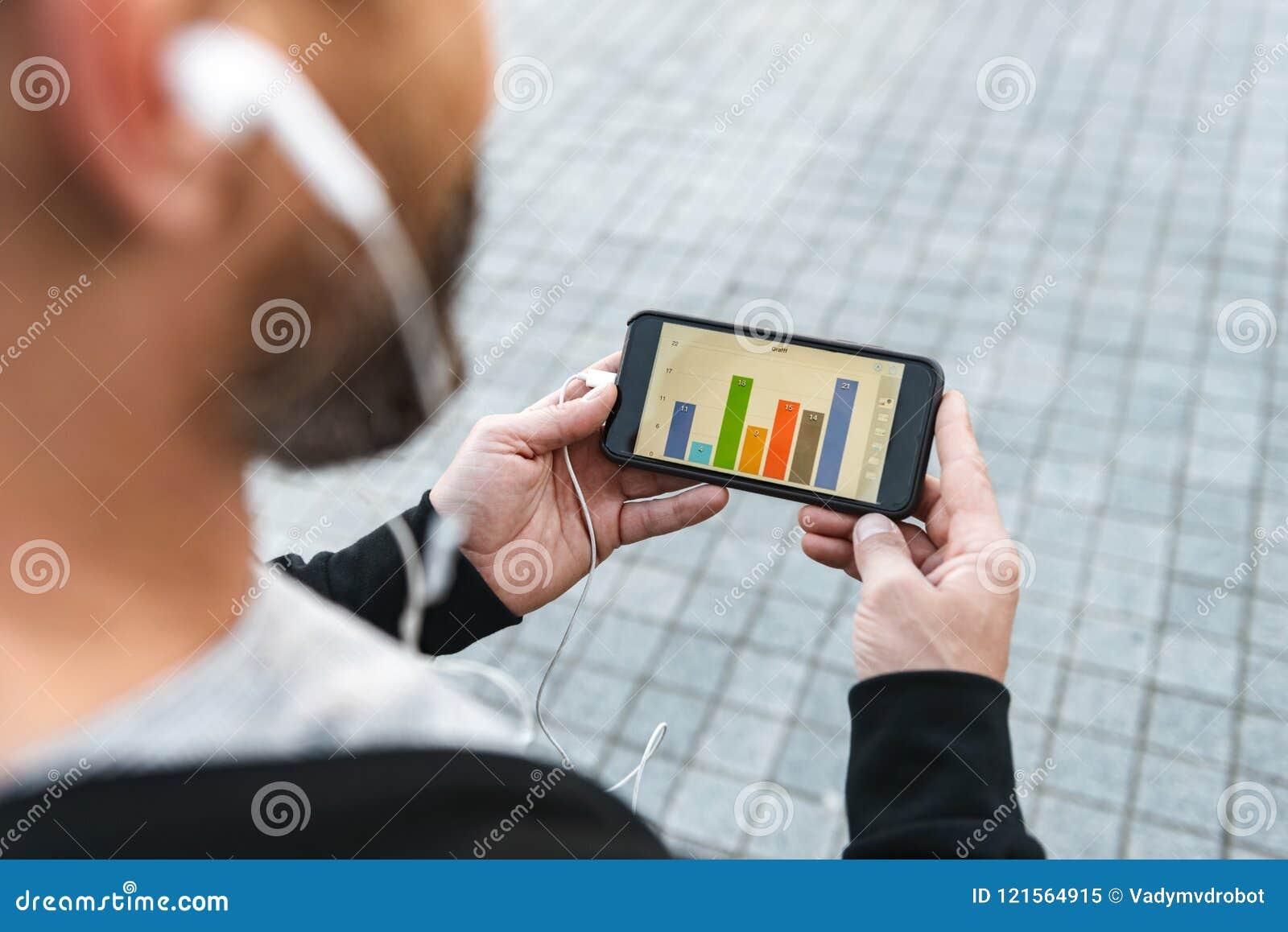 Foto cosechada del deportista maduro que usa el teléfono móvil