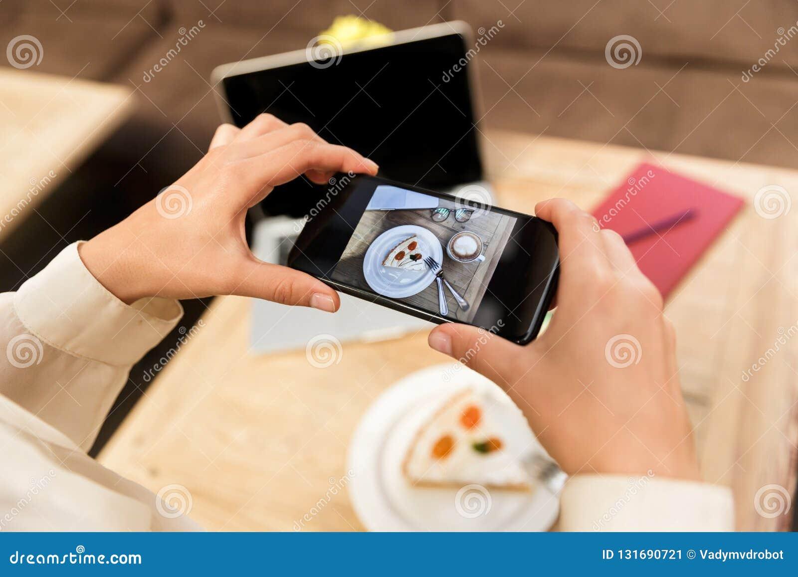 Foto cosechada del sombrero que lleva de la mujer caucásica que fotografía la comida en el teléfono celular