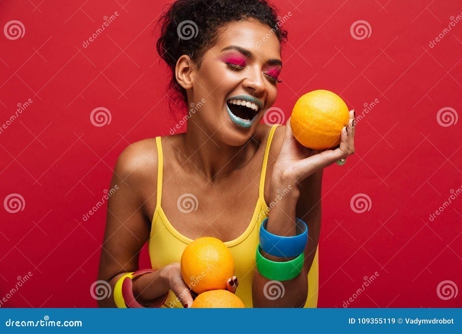 A foto da forma do alimento da mulher alegre da misturado-raça com colorido faz