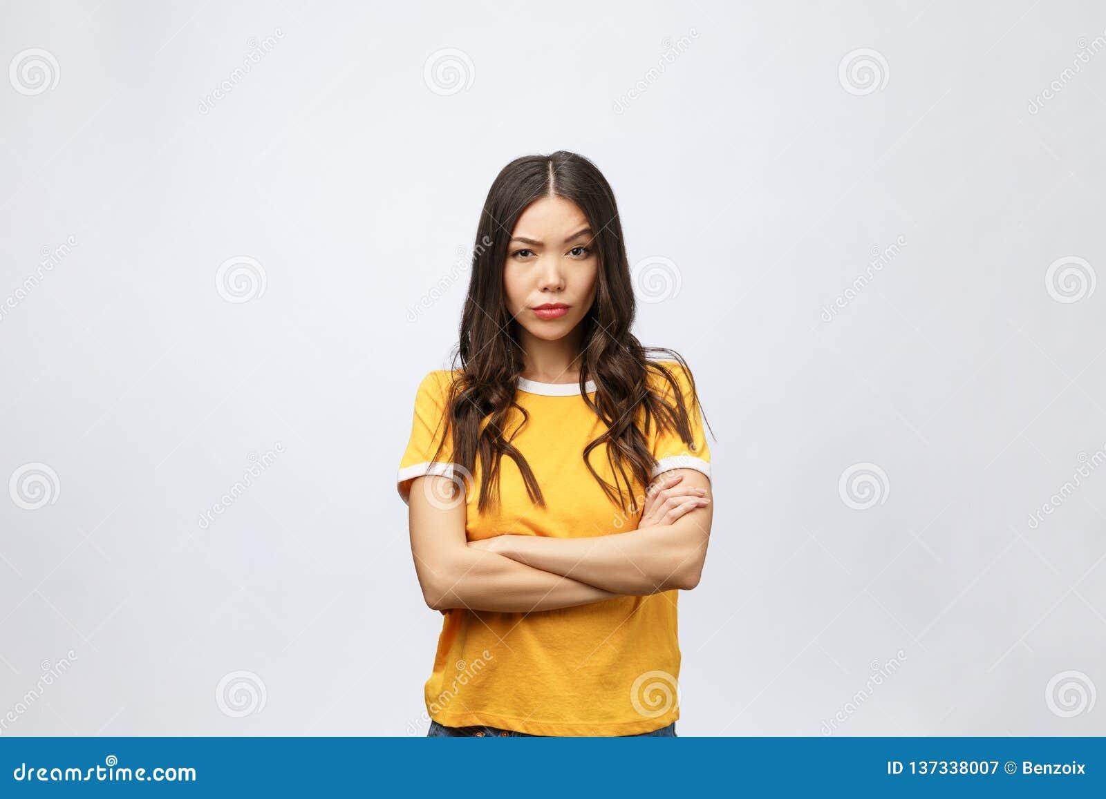 A foto da jovem senhora séria com braços cruzou-se vestido na posição azul do vestido e no levantamento sobre o fundo branco