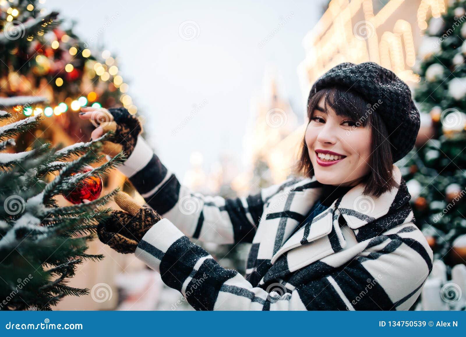 Foto da mulher feliz perto da árvore de Natal pintada na rua