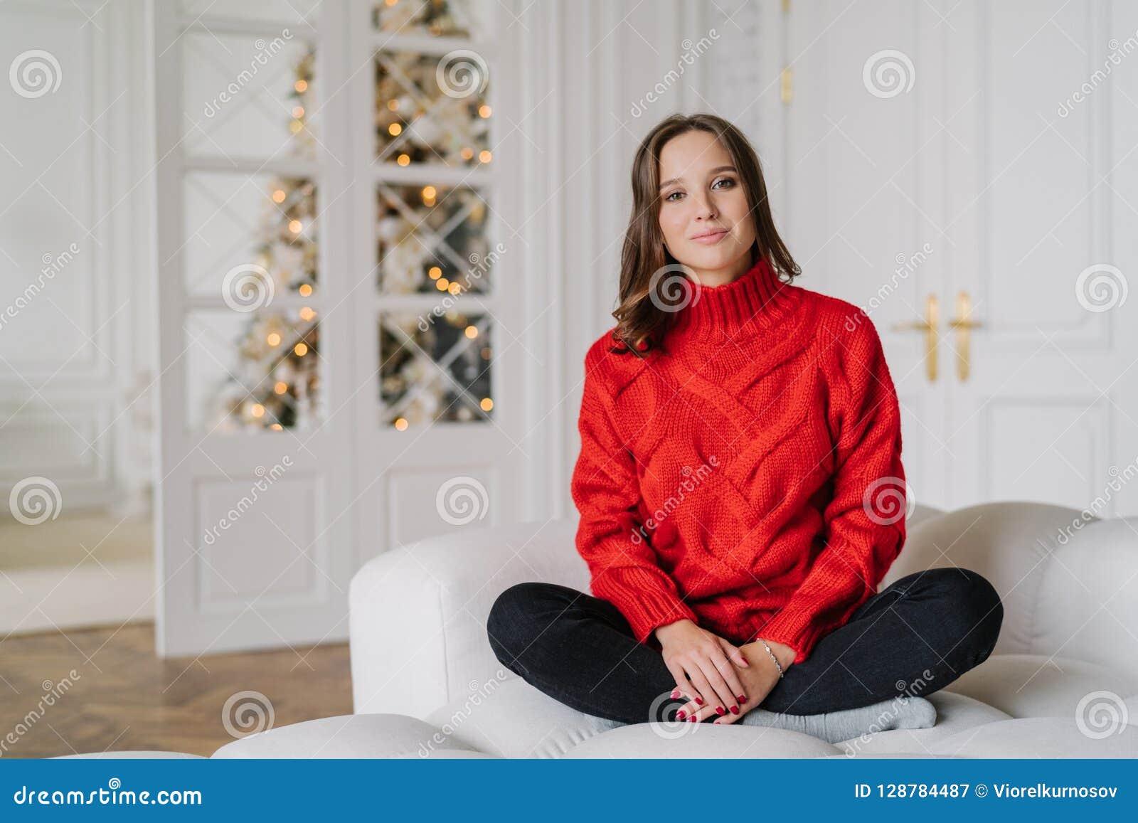 A foto da mulher parecendo jovem agradável vestida na camiseta vermelha, calças, senta os pés cruzados no sofá confortável, aprec