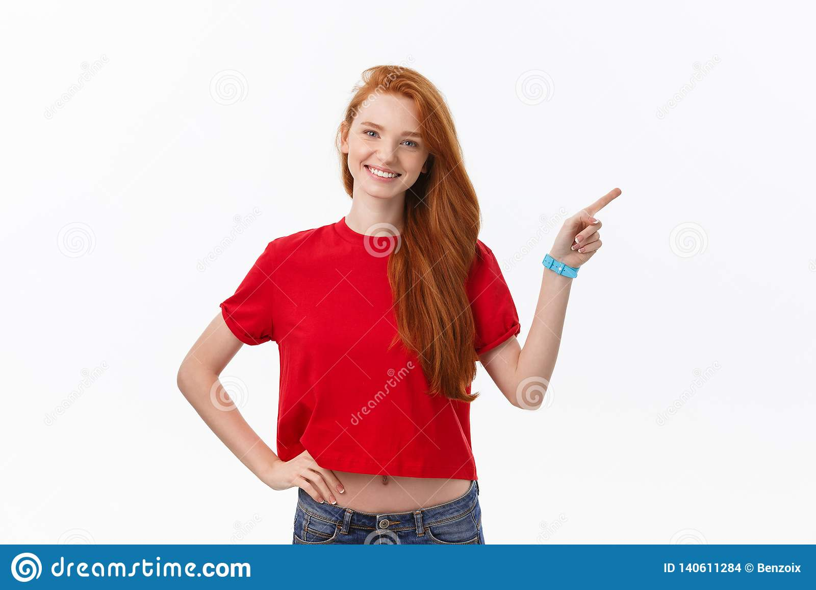 Foto da posição feliz da jovem mulher isolada sobre o fundo branco da parede Olhando a câmera que mostra apontar do copyspace