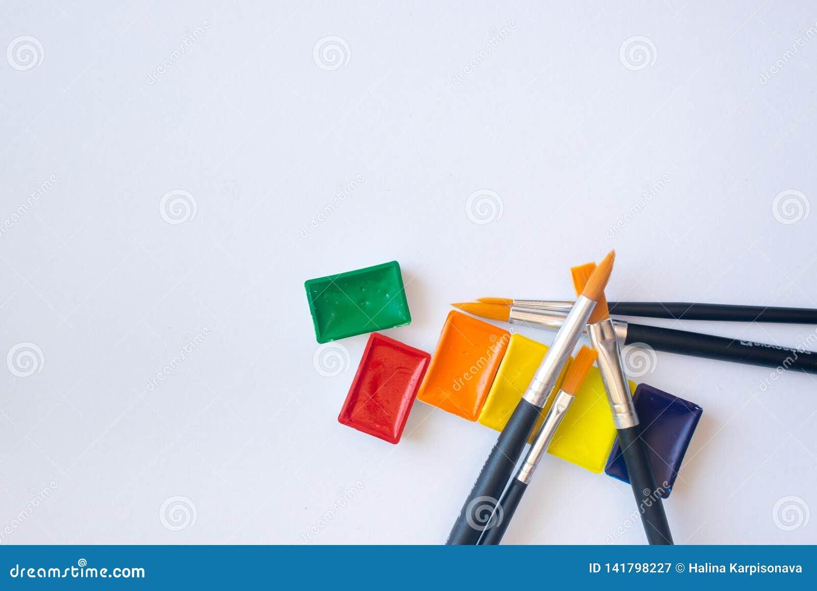 Foto da vista superior de pinturas da aquarela em umas cubetas com as escovas para a pintura da cor de água