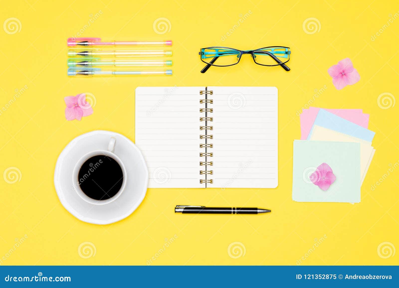 Foto da vista superior da mesa de escritório com da placa da zombaria o bloco de notas, a pena, vidros e o copo abertos acima for