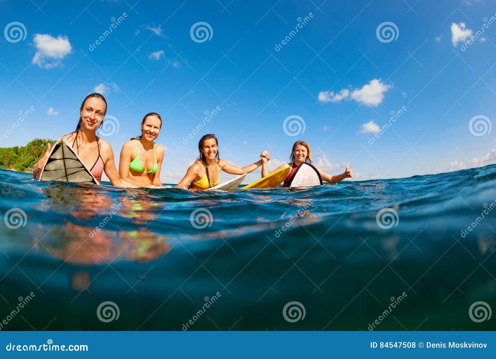 Foto das meninas felizes do surfista que sentam-se em placas de ressaca