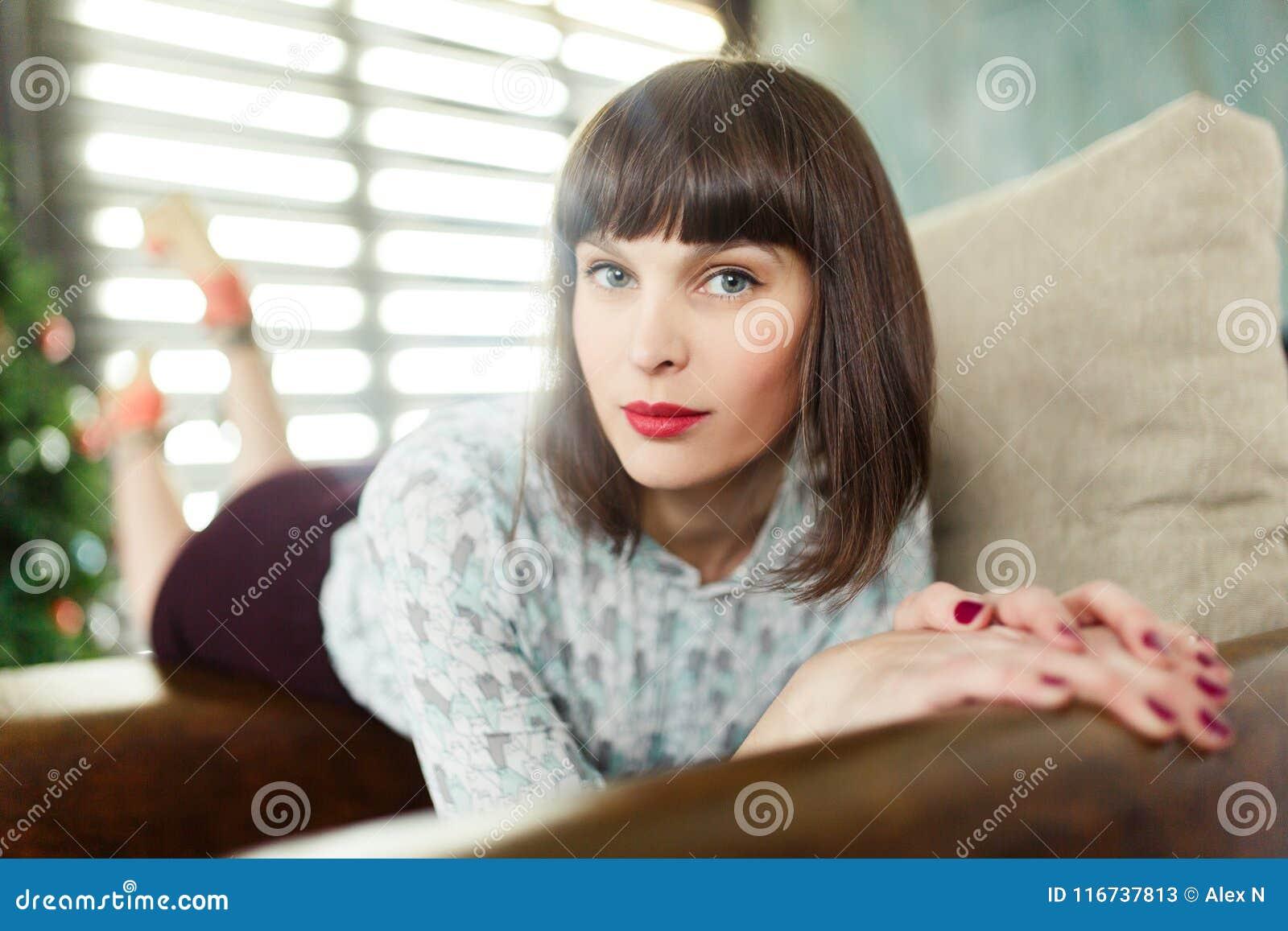 Foto de la morenita joven que se sienta en silla cerca de ventana con las persianas