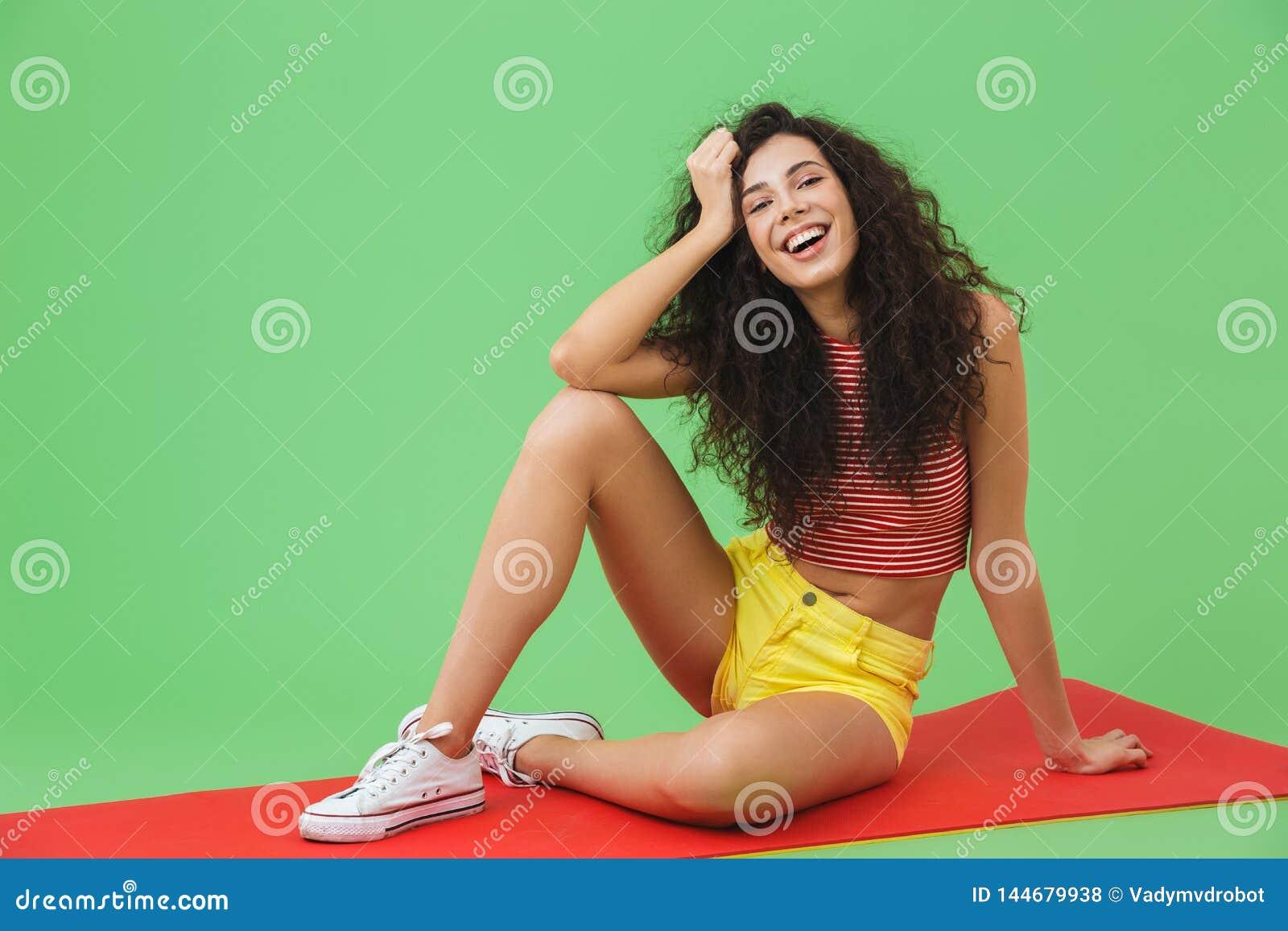 Foto de la mujer europea 20s de la aptitud que sonríe y que se sienta en la estera de la yoga durante aeróbicos